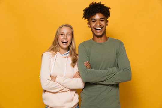Photo of happy students man and woman 16-18 with dental braces laughing at camera, isolated over yellow background