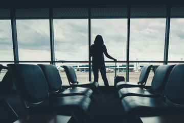 Silhouette tourist woman is talking on mobile phone while standing in passengers airport terminal