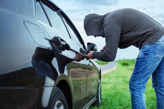 car thief in action, a man in a hood breaks a screwdriver car door