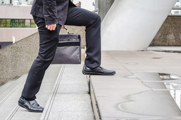 first morning of close up view of foot Businessman walking up the stairs in a rush hour to work. Hurry time.working man,business promotion concept, business successful