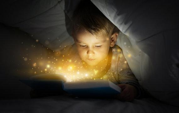 Cute little boy reading book in bed under blanket