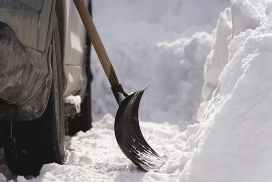 Snow shovel on a car during winter