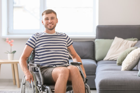 Happy young man in wheelchair at home