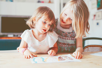 two female siblings children indoor drawing on a paper - playing, drawing activities, creativity concept