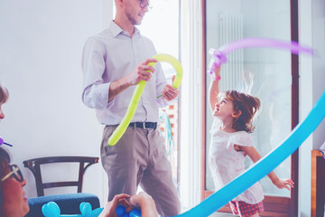 single father playing indoor with her daughter with balloon - happiness, weekend activities, bonding concept