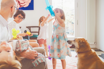 family indoor playing with balloon toys - happiness, bonding, innocence concept