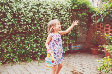 female child outdoor playing with bucket having fun - happiness, carefree, excitement concept