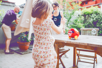 from behind female child playing with bubble soap - having fun, happiness, enjoying concept