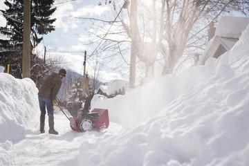 Man using snow blower machine in snowy region