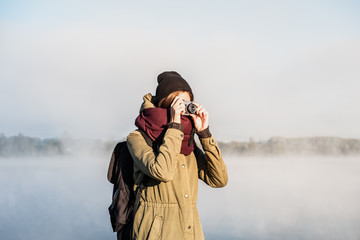 Female hiker photographing beautiful nature scenery covered in fog. Woman uses a vintage film camera standing in gorgeous nature park at dawn