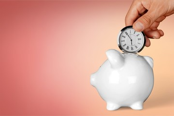Hand depositing clock in piggy bank