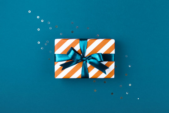 Gift box wrapped in red striped paper and tied with aqua blue bow on aqua blue background decorated with sparkles. Christmas card concept.