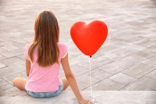 Cute little girl with heart-shaped air balloon sitting on stairs outdoors