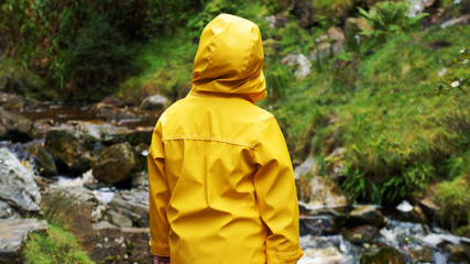 Back of a Small Person wearing a Yellow Rain Coat