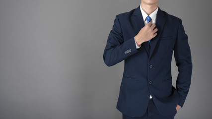 close up of business man in blue suit is confident on gray background