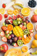 Variety of cut fruits and berries platter, strawberries blueberries, mango orange, apple, grapes, kiwis on the white wood background, copy space for text, layout, top view, selective focus