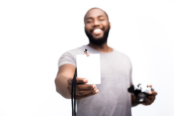 A young, self-confident journalist of an African-American national identity shows his press certificate, a reporter for a photo reportage at the event. White background, place to insert company logo