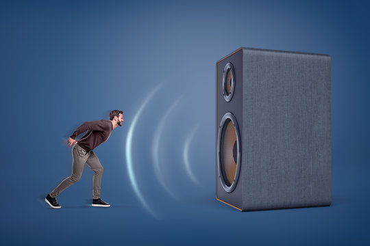 A large vintage speaker emits strong sound-waves and almost sweeps a small aggressive man off his feet.