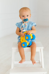 Сute baby girl in blue jeans holding yellow elephant. Little toddler sitting on the white wooden chair with pacifier in mouth. Portrait of one year child