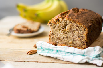 Banana bread loaf with pecans on a wooden table