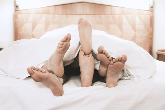 three pairs of feet lying together under bed cover in bedroom, threesome group sex concept, filtered image