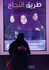 A Saudi student uses her phone at the exhibition to guide job seekers at Women's Career Fair in Riyadh