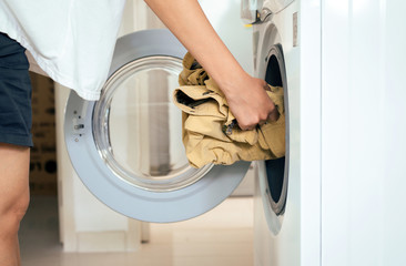 Woman hand push clothes from washing machine at house