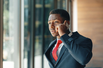 african american businessman talking on mobile phone in modern office