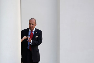 White House economic adviser Larry Kudlow is handed a cellphone from an aide while walking to an interview with Fox News at the White House in Washington