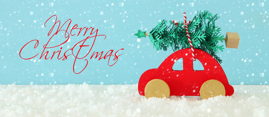 Wooden red car carrying a christmas tree in front of blue background.