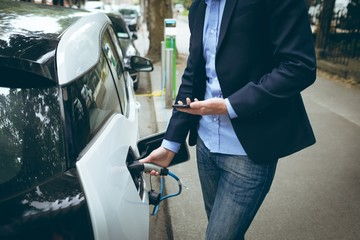 Businessman using mobile phone while charging electric car