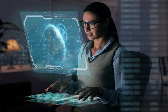 Close up of a beautiful girl with glasses while she is working with a futuristic computer with holograms. Concept: Future, technology, work