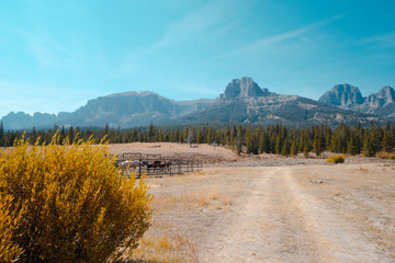 Horse corral and dirt road near Dubois Wyoming in the Shoshone National Forest with view of Rocky Mountains in the fall