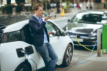 Businessman talking on mobile phone while charging electric car