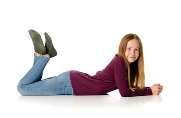 Young teen girl lying on white background