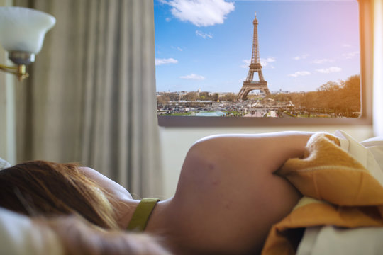 Woman stretching in bed after waking up and looking out of window, back view.
