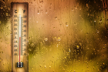 Obraz Thermometer behind the drops window shows a low temperature - fototapety do salonu
