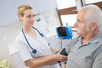 female doctor checking old man patient arterial blood pressure