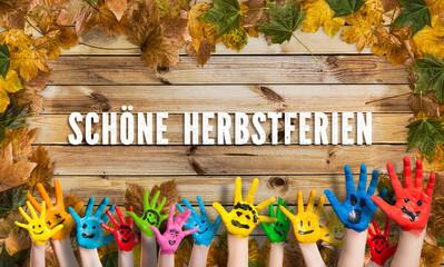 """in bunten Farben angemalte Kinderhände herbstlich dekoriertem Holzschild und der Aufschrift """"Schöne Herbstferien"""""""