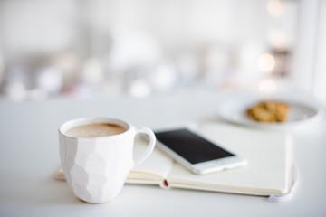 Modern white office, designer handmade cup of coffee, smartphone