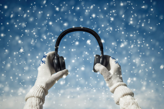 Female hands in the winter mittens with a headphones on the winter snowfall background. Concept.