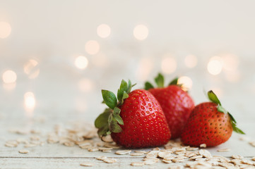 Fresh strawberry and raw oats on wooden table, blurred lights as background