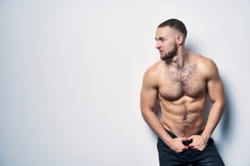 Shirtless muscular man in jeans standing at white wall posing looking to side at blank copy space