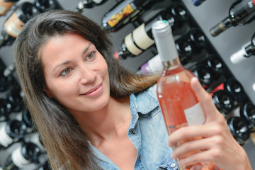 Lady looking at bottle of rose wine