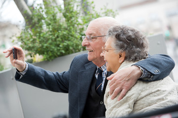joyful senior couple taking selfie
