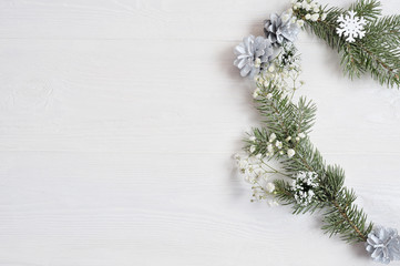 Mockup of Christmas Wreath in form of heart Decorated with white snowflakes and cones. On white wooden background