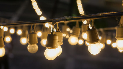 Bright festival garland light bulbs hanging over outdoor shopping area copy space