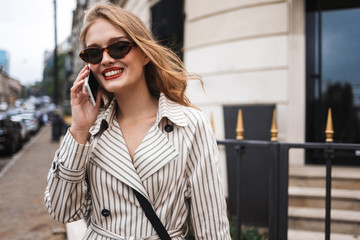 Young pretty smiling woman in striped trench coat happily talking on cellphone while walking around cozy city street