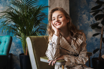 Young cheerful woman with wavy hair in striped trench coat leaning on hand happily looking in camera while spending time in modern cafe
