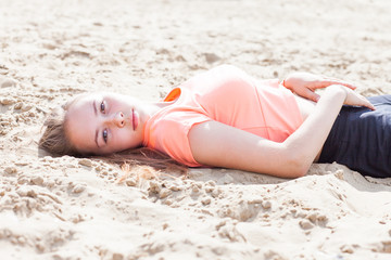 The girl is lying on the sand